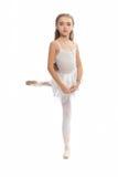 La chica joven en su danza viste alcanzar abajo para tocar su pie Fotos de archivo libres de regalías