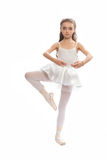 La chica joven en su danza viste alcanzar abajo para tocar su pie Foto de archivo