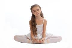 La chica joven en su danza viste alcanzar abajo para tocar su pie Foto de archivo libre de regalías