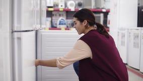 La chica joven en sus 20 que el ` s sube a un refrigerador en ferretería abre el congelador y comprueba hacia fuera qué ` s dentr almacen de metraje de vídeo