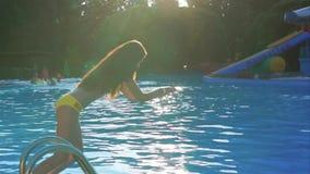 La chica joven en un bañador se zambulle en la piscina, saliendo de un chapoteo del agua almacen de metraje de vídeo