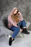 La chica joven en un chándal se sienta en un interior elegante imagen de archivo libre de regalías