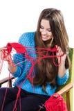 La chica joven en un suéter azul se sienta en una silla con una bola roja del hilado y de hacer punto una bufanda y un perro de P Imagen de archivo libre de regalías