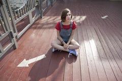 La chica joven en un suéter rojo de las lanas y pantalones cortos de los vaqueros se está sentando en el embarcadero Foto de archivo
