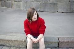 La chica joven en un suéter rojo de las lanas y pantalones cortos de los vaqueros se está sentando en los pasos Imagen de archivo libre de regalías
