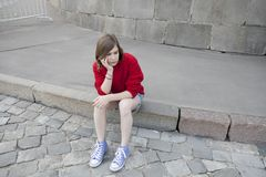 La chica joven en un suéter rojo de las lanas y pantalones cortos de los vaqueros se está sentando en los pasos Imágenes de archivo libres de regalías