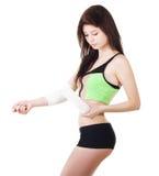 La chica joven en un top sin mangas y pantalones cortos de los deportes está vendando su brazo con un vendaje elástico Foto de archivo libre de regalías