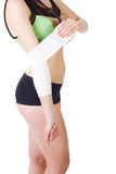 La chica joven en un top sin mangas y pantalones cortos de los deportes está vendando su brazo con un vendaje elástico Imagen de archivo libre de regalías
