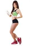 La chica joven en un top sin mangas y pantalones cortos de los deportes está vendando su brazo con un vendaje elástico Fotografía de archivo