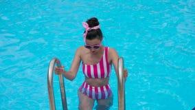 La chica joven en un traje de baño rosado rayado desciende en la piscina metrajes