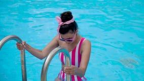 La chica joven en un traje de baño rosado rayado desciende en la piscina almacen de video