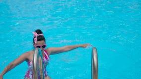 La chica joven en un traje de baño rosado rayado desciende en la piscina almacen de metraje de vídeo