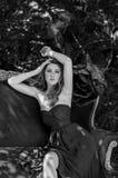 La chica joven en un vestido de noche largo se está sentando en un sofá en el bosque Fotografía blanco y negro fotos de archivo libres de regalías