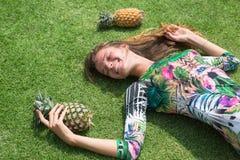 La chica joven en un vestido verde, un lezhitna encendido enarena con las piñas en manos, la muchacha de moda con las piñas Fotografía de archivo
