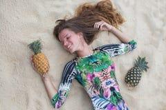 La chica joven en un vestido verde, un lezhitna encendido enarena con las piñas en manos, la muchacha de moda con las piñas Foto de archivo libre de regalías