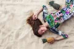 La chica joven en un vestido verde, un lezhitna encendido enarena con las piñas en manos, la muchacha de moda con las piñas Foto de archivo