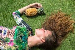 La chica joven en un vestido verde, un lezhitna encendido enarena con las piñas en manos, la muchacha de moda con las piñas Fotos de archivo