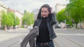 La chica joven en una chaqueta de cuero negra y una bufanda gris se coloca en el fondo de una calle de la ciudad Ella r?e metrajes
