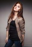 La chica joven en una chaqueta de cuero representa el modelo Foto de archivo