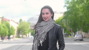 La chica joven en una chaqueta negra de cuero se coloca en el fondo de una calle de la ciudad almacen de metraje de vídeo