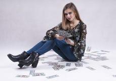 La chica joven en vaqueros se sienta con los dólares fotografía de archivo