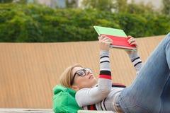 La chica joven en vidrios miente con su Tablet PC foto de archivo