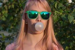 La chica joven en vidrios verdes con el pelo largo sopla burbuja del chewi fotos de archivo libres de regalías