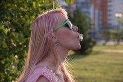 La chica joven en vidrios verdes con el pelo largo sopla burbuja del chewi Imagen de archivo