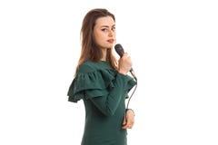 La chica joven encantadora canta en Karaoke con el micrófono a disposición Imagen de archivo