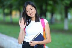 La chica joven entra en el parque que camina mirando la cámara y las ondas Foto de archivo