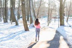 La chica joven entra para los deportes en parque del invierno Fotos de archivo