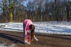 La chica joven entra para los deportes en parque del invierno Imagenes de archivo