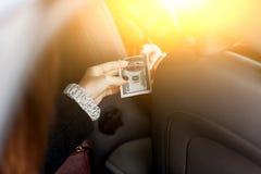 La chica joven envía el dinero al conductor en taxi Imagen de archivo libre de regalías