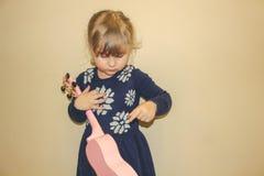 La chica joven envejeció 3 a 5 años que llevaban a cabo un ukelele y que aprendían cómo jugarlo en un vestido lindo Pelo caucásic fotografía de archivo