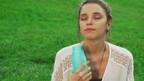 La chica joven es agua potable mientras que hace yoga almacen de metraje de vídeo