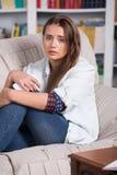 La chica joven es el sentarse gritador en el sofá Foto de archivo