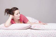 La chica joven es mentira triste en cama Fotografía de archivo