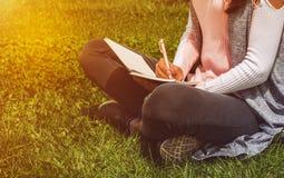 La chica joven escribe con la pluma en el cuaderno que se sienta en hierba verde en parque Foto de archivo libre de regalías