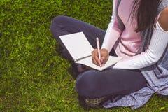 La chica joven escribe con la pluma en el cuaderno que se sienta en hierba verde en parque en prado Fotografía de archivo