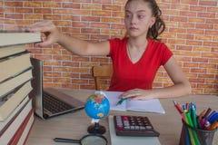 La chica joven escribe en cuaderno entre los libros Muchacha que trabaja en su preparación estudiante atractivo joven Girl que es foto de archivo libre de regalías