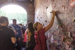 La chica joven escribe una letra a Juliet en la pared en el paso t Imagen de archivo libre de regalías