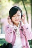La chica joven escucha la música Imágenes de archivo libres de regalías