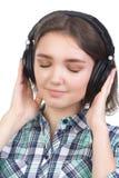 La chica joven escucha la música con los auriculares aislados en blanco Fotografía de archivo