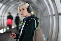 La chica joven escucha la música en auriculares grandes en el subterráneo Imágenes de archivo libres de regalías