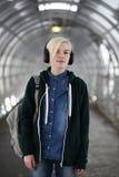 La chica joven escucha la música en auriculares grandes en el subterráneo Fotografía de archivo