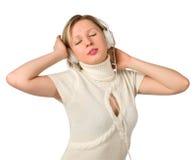 La chica joven escucha la música en los auriculares Imágenes de archivo libres de regalías