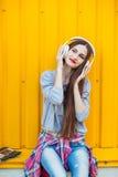 La chica joven escucha la música en los auriculares blancos Fotos de archivo libres de regalías