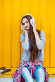 La chica joven escucha la música en los auriculares blancos Foto de archivo libre de regalías