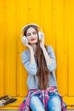 La chica joven escucha la música en los auriculares blancos Fotos de archivo