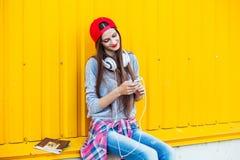 La chica joven escucha la música en los auriculares blancos Fotografía de archivo libre de regalías